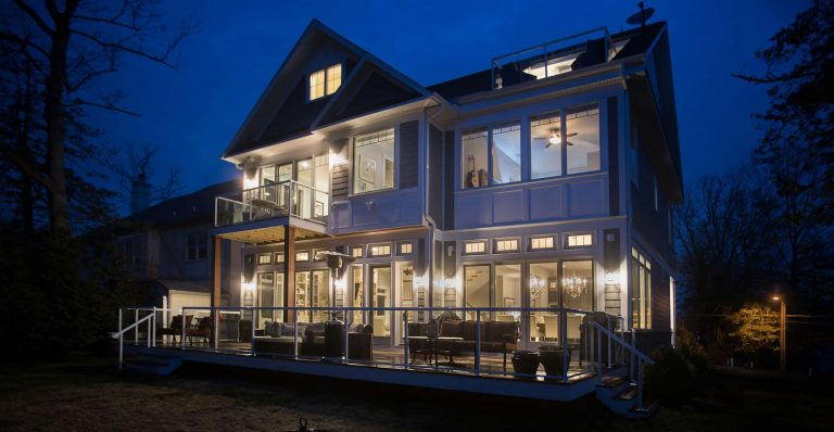 A brightly lit custom home with a deck at night