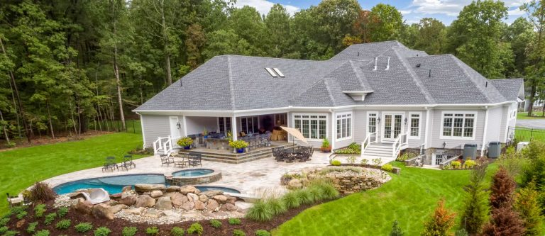 A custom home with stone patio and water feature