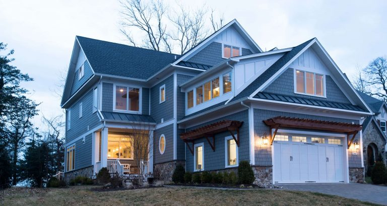 A custom home with lots of exterior lighting at dawn