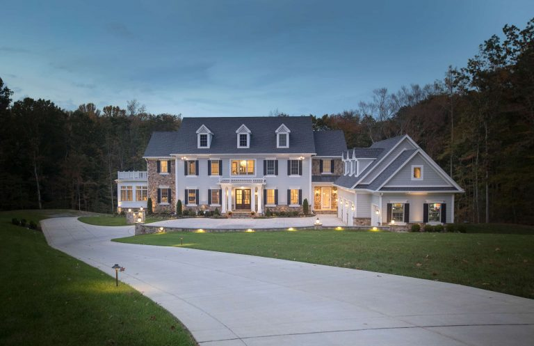 A large custom home with a winding driveway at dusk